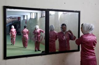 Hatifa Rezai , a student of the Shaolin Wushu club, is reflected in a mirror as she adjusts her scarf before her exercise in Kabul, Afghanistan.