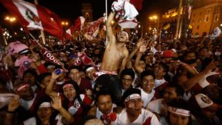 A large crowd of Peruvian fans wave their flags as a shirtless man is carried shoulder high