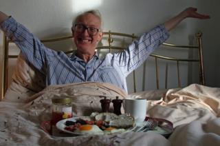 An older man eats breakfast in bed.
