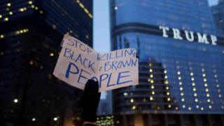 "Placard saying ""stop killing black and brown people"" in front of Trump tower"