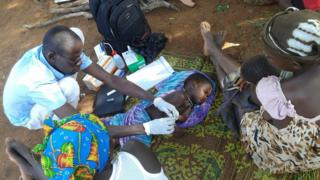 Nurses diagnosing malaria fevers in children in Burkina