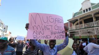 """Protesters in Harare, Zimbabwe, one holding a """"Mugabe must go"""" sign - Wednesday 3 August 2016"""