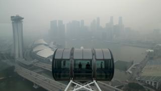 Tourists sit in a capsule on the Singapore flyer observatory wheel overlooking the skyline of the central business shrouded by haze in Singapore September 10, 2015