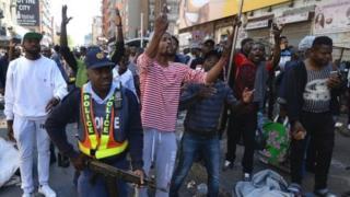 Polisi berusaha melumpuhkan para perusuh yang menjarah toko dan membakar mobil.