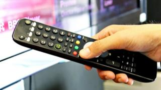 Person using TV remote control