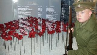 Young lad wearing military uniform in front of poppies and roll of honour