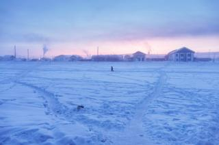 A man walks in the village at sunrise. The climatic factor is here omnipresent: in February 1892, the lowest temperature in the world (Antarctica not included) was recorded in Verkhoyansk. And if the village is fighting over the title of the coldest village in the world with Oymyakon, it nevertheless holds the record of the greatest temperature range on Earth: 105°C (189°F) with -67,8°C in winter and 37,3°C in summer.