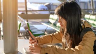 Una mujer con un teléfono celular en un aeropuerto.