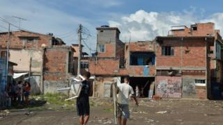 Jovens caminham pela favela do metrô mangueira