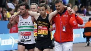Matthew Rees ayuda a David Wyeth, junto a un oficial de la organización, a cruzar la meta en la maratón de Londrés