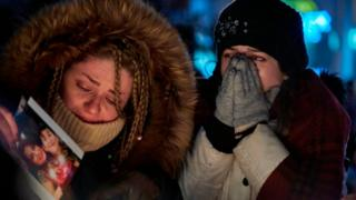 Two women cry during vigil for Canadian victims of Iran air crash