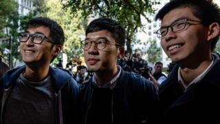 Three young men smile outside the court in Hong Kong earlier in January