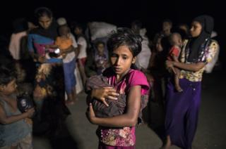 Rohingya Muslims fleeing violence in Myanmar hold children and belongings.