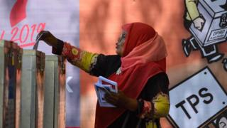 A woman casts her ballot in Indonesia in a pre-election drill