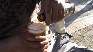 A man pouring a beer at a shebeen in South Africa