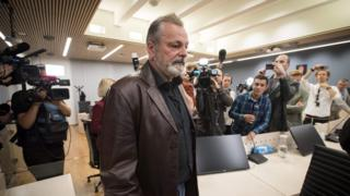 Eirik Jensen arrives at court, surrounded by news media pointing cameras, on 18 September