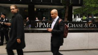 People walk past as others protest outside of the New York City headquarters of JPMorgan Chase on May 11, 2017 in New York City