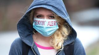 "Young woman wearing a face mask with the words ""stayin' alert"" on it"