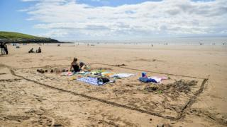 A woman sits alone in an area marked in the sand on Barry Island beach, Wales.