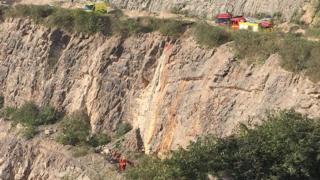 A wide shot of the quarry and the rescue operation