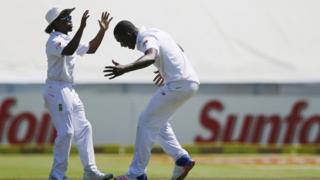 South African bowler Kagiso Rabada (R) congratulates South Africa's fielder Temba Bavuma during the second Test match against England on January 2, 2016