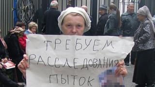 "Elena Urlaeva holds up poster saying ""We demand an investigation into torture"""