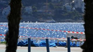 Dead bodies covered with blue sheets are pictured on the Promenade des Anglais seafront in the French Riviera city of Nice on 15 July 2016,