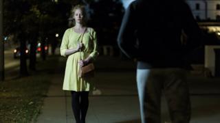 Mujer con miedo caminando de noche pro la calle