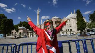 "A woman wrapped in a Turkish national flag gestures outside the Hagia Sophia museum on July 10, 2020 in Istanbul as people gather to celebrate after a top Turkish court revoked the sixth-century Hagia Sophia""s status as a museum, clearing the way for it to be turned back into a mosque"