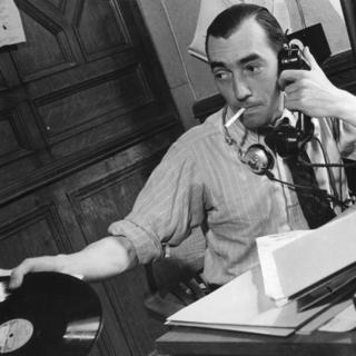 Periodista en el Servicio Latinoamericano hablando por teléfono y con un disco de pasta en la mano, en 1940