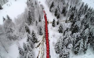 Luftfoto, welches die Leute trägt eine riesige türkische Flagge durch eine schneebedeckte Landschaft zeigt