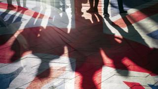 People's shadows over Union flag
