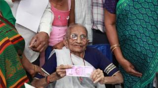 """Indian Prime Minister, Narendra Modi""""s mother Heera Ba Modi (C) holds up a 2,000 rupee note after exchanging money at a bank in Rysan village, near Gandhinagar, some 30 kms from Ahmedabad on November 15, 2016."""