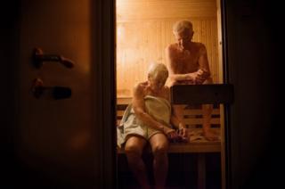 An elderly couple sit in a sauna.