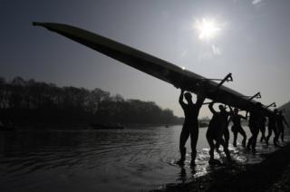 El equipo de remo de la Universidad de Oxford cargan su embarcación fuera del agua, después de una sesión de entrenamiento en el río Támesis