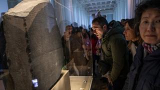 El público observa la piedra de Rosetta.
