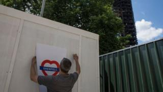 man puts up heart shaped Grenfell poster in the shadow of the burnt out tower