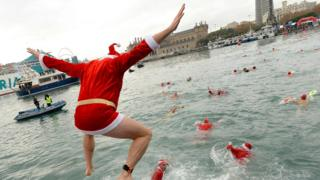 """A participant in a Santa Claus costume jumps into the water during the 108th edition of the """"Copa Nadal"""" (Christmas Cup) swimming competition in Barcelona's Port Vell on December 25, 2017"""