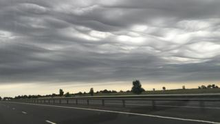 Wavy grey clouds above a motorway