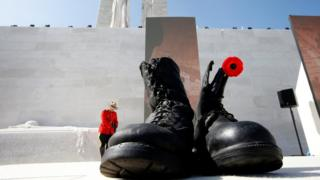 Military boots symbolising dead soldiers are seen as a Canadian police mounted officer stand guards before the ceremony to commemorate the 100th anniversary of the battle of Vimy Ridge, at Canadian National Memorial in Vimy, France, April 9, 2017