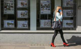woman walks past estate agents