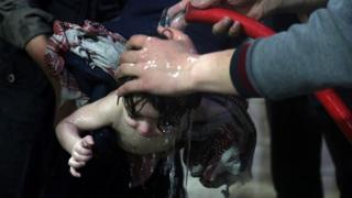 A child is washed with a hose at a hospital in Douma, eastern Ghouta in Syria, after a suspected chemical attack (7 April 2018)