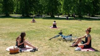 Two women observe social distancing whilst enjoying the hot weather in Greenwich Park, London on Wednesday 20 May