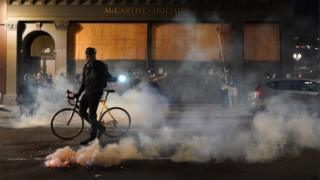A demonstrator with a bicycle moves past a gas canister in the road near the courthouse in Portland