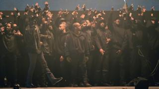 Kanye West on stage at the Brits with grime artists behind him