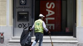 Street cleaner outside a shop and bank ATM in Athens, on 13 July 2015