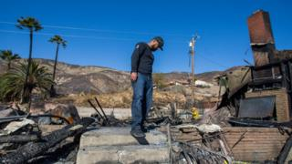 in_pictures Matthew Valdivia looks for personal objects among the ashes of his home at Viento Way bear San Bernardino, California, on 31 October