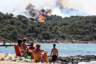 People on the beach watch a forest fire in La Croix-Valmer, near Saint-Tropez, on 25 July 2017.