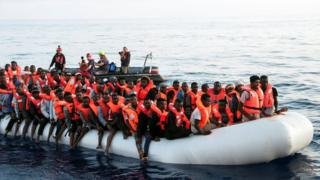Migrants are seen in a rubber dinghy as they are rescued by the crew of the Mission Lifeline rescue boat in the central Mediterranean Sea, 22 June 2018