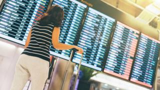 Woman standing in front of departure board